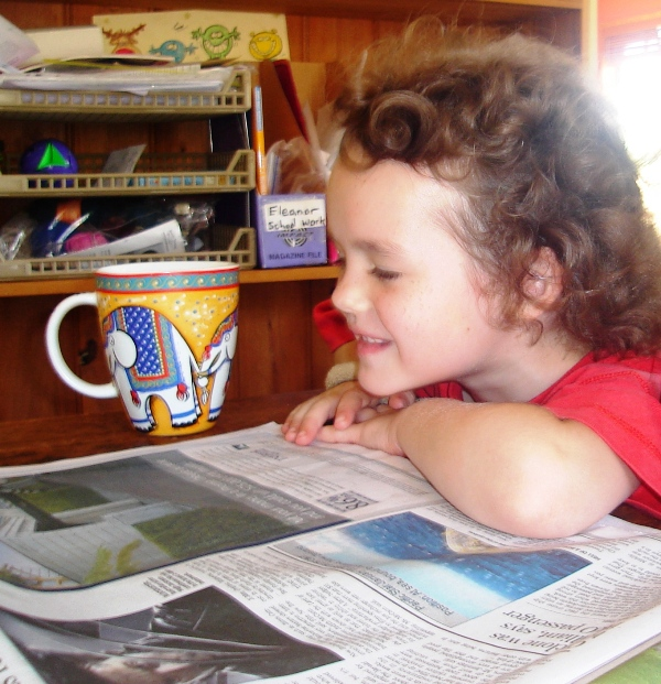 young child reading newspaper